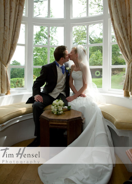 Tim Hensel photographer in Kent copyright couple sitting in bay window seat having a kiss just after ceremony aw
