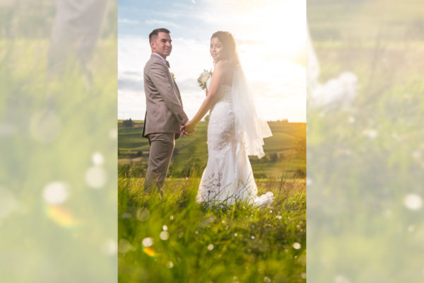Photographer in Kent snaps couple in wedding outfits looking back at camera in Kent