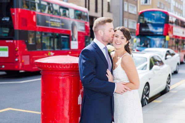 Just married couple in duit and white dress kissing in front of red pillar box Wedding photographer Folkestone Tim Hensel copyright