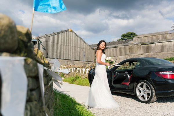 Bride with long brown hair looking back at camera in front of Kent barn, copyright Tim Hensel photographer in Kent