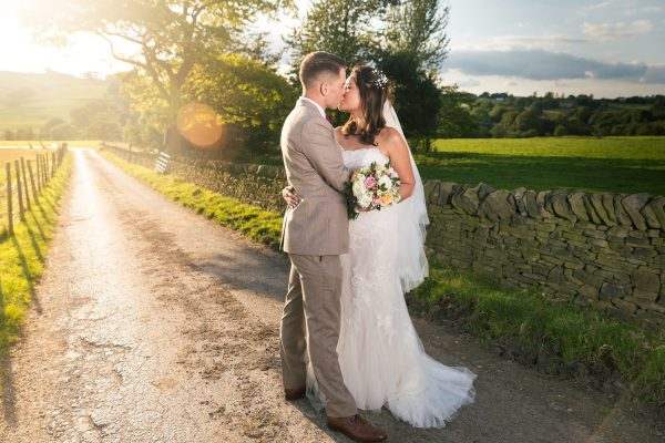 Just married couple kissing on country lane, copyright Tim Hensel photographer in Kent