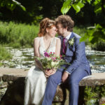 Brunette couple kissing on wall next to river mauve bouquet blue suit Wedding photographer Folkestone Tim Hensel copyright