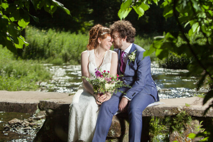 Summer wedding themes a couple kissing on wall next to river mauve bouquet blue suit Wedding photographer Folkestone Tim Hensel copyright