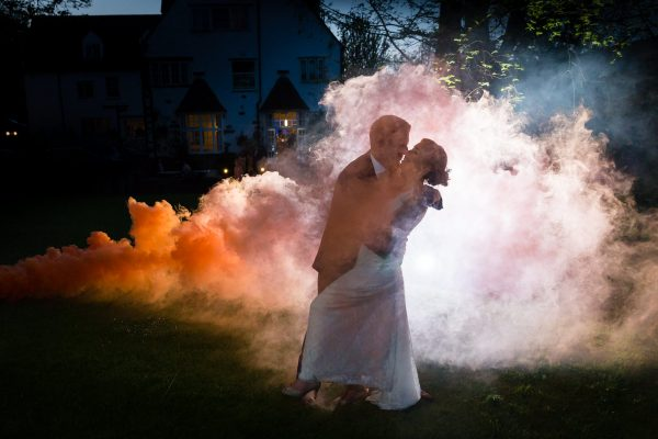 Wedding photographer Ashford couple against orange smoke
