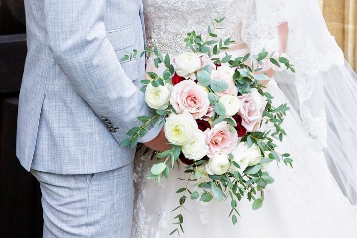 Picture of a bride and groom holdingroses property of Emily&Me florist Folkestone